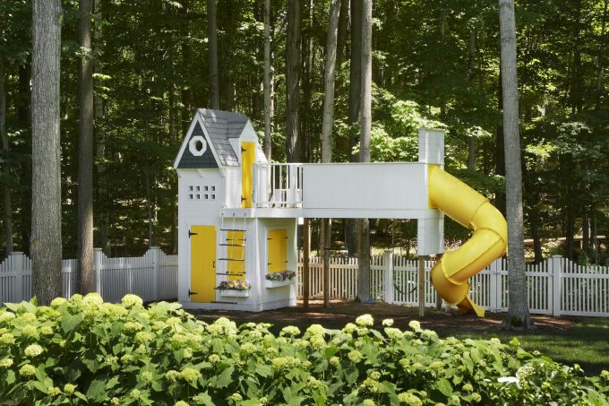 Yellow Accents On Playhouse In Kids Play Area With Swing Sets Plus Wood Trim As Picket Fence For Backyard Design Ideas In Forest Around With Air Fresh Because Flowers Plant