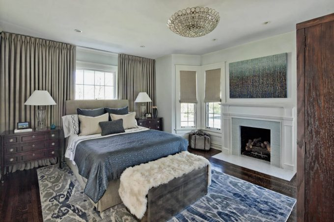 Abstract Art Above Fireplace Also Glass Table Lamps On Bedside Dressers With Brown Upholstered Bed In Traditional Bedroom With Dark Stained Wood Floor Plus Ikat Rug And Tall Windows