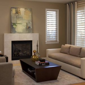 Abstract Art In Contemporary Living Room With Bamboo Floor And Custom Sofa Also Limestone Fireplace Surround Plus Swivel Chairs With Hunter Douglas Blinds Also Throw Pillows And Wood Coffee Table