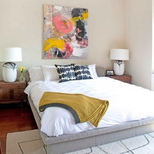 Abstract Artwork On Beige Wall And Black And White Throw Pillow On Platform Bed For Modern Bedroom Plus Sketch Rug And White Bedding Also White Table Lamp On Wood Nightstand
