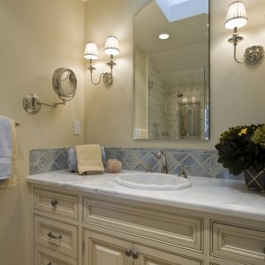 Accent Tile And Sconce On Beige Wall Plus Blue Tiles Also Cabinetry With Carrara Marble And Door Handles Also Drawer Pulls With Beveled Mirror And Overmount Sink Also Wall Tile Design