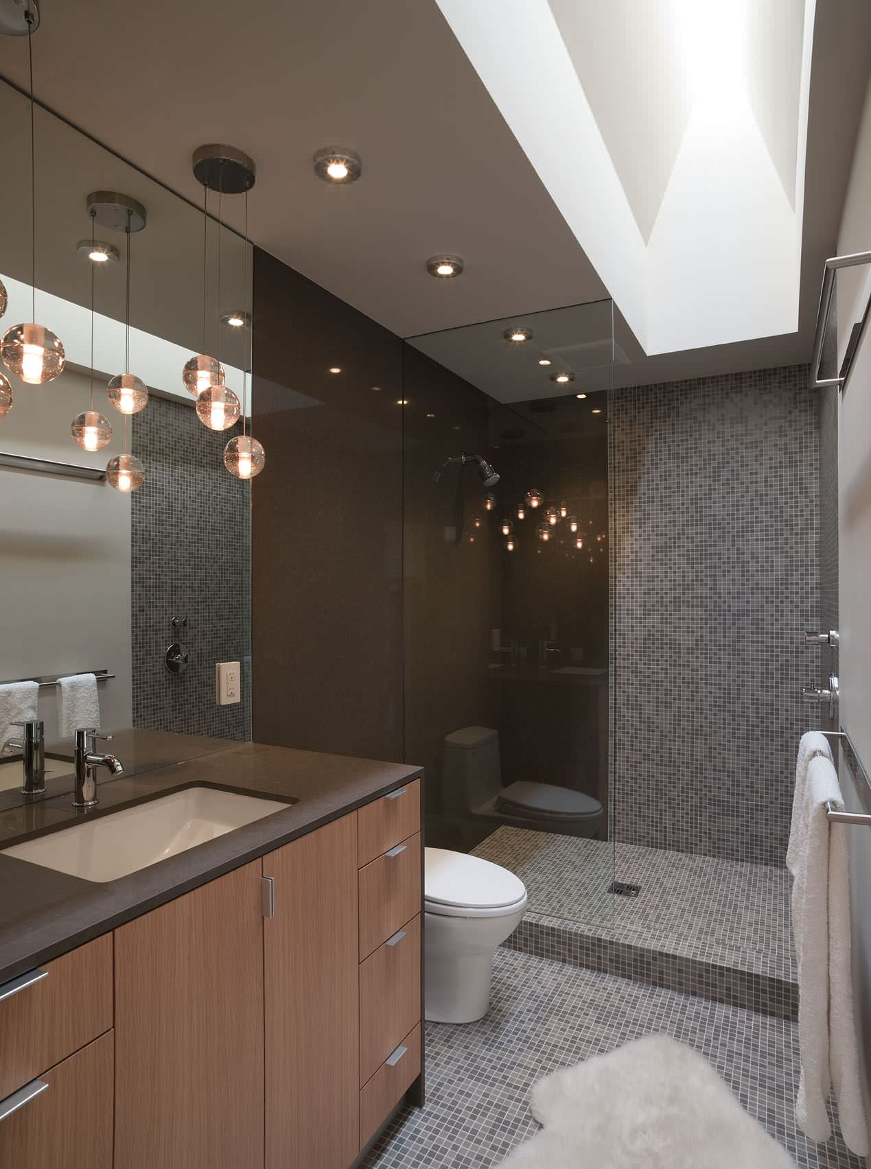 Remodel Bathroom Ideas Using Glass Shower Enclosures: Accent Wall And Glass Shower Enclosures Plus Sheepskin Rug In Minimalist Bathroom With Mosaic Tiles And Open Shower Plus Skylights Also Bathroom Lighting Ideas With Wood Cabinets Plus Undermount Sink