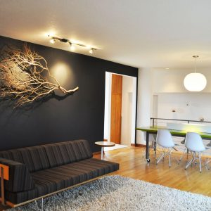 Amazing Accent Wall With Branches Plus Ceiling Lighting And Dark Wall Also Globe Pendant In Midcentury Living Room With Interior Design Plus Modern Daybed And Wood Flooring