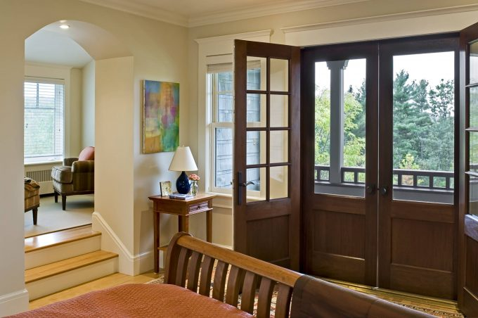 Arched Doorway Also Crown Molding Plus French Doors In Master Bedroom With Neutral Colors And Screen Doors Plus Wall Decor Also Wood Bed With Wood Flooring And Cordless Table Lamp