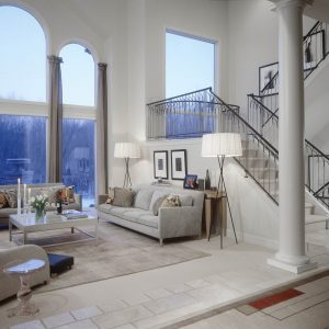 Arched Windows In Transitional Family Room With Area Rug And End Table Plus Floor Lamp Also Gallery Wall With Staircase And Translucent Furniture Plus Decorative Pillows For Couches