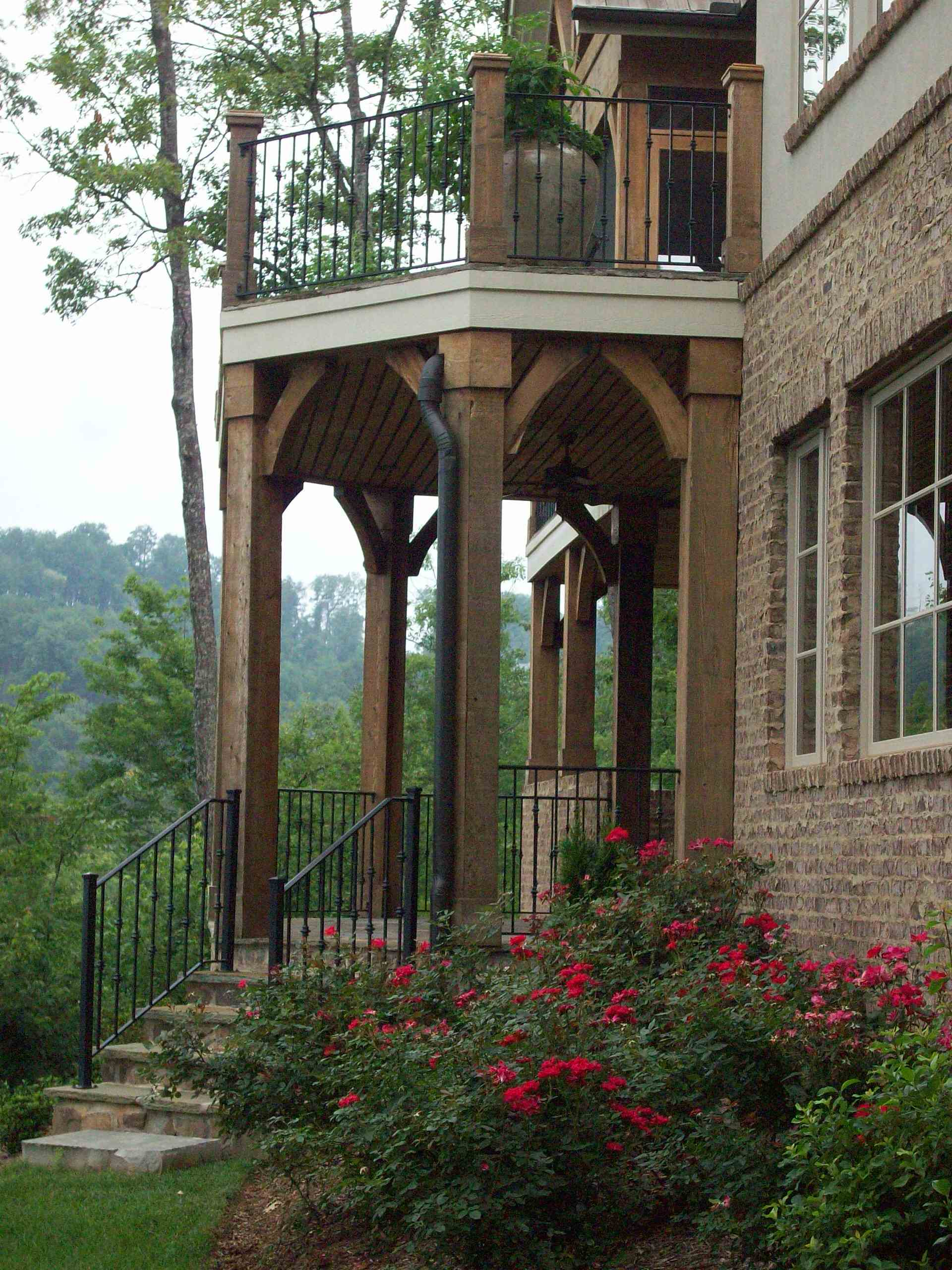 Inspiring Iron Railings Design for Staircase at Your Home: Arches And Balcony With Brick For Traditional Exterior Plus Foundation Planting Also Potted Plant With Roses And Iron Railings Also Wood Ceiling Plus Windows With Concrete Stair And Small Garden