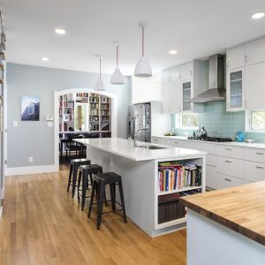 Archway In Contemporary Kitchen With Engineered Wood Flooring Plus Black Bar Stool And Blue Tile Backsplash Also Butcher Block Countertop With Cookbook Shelves And Gray Kitchen Island