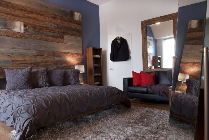 Area Shag Rug And Barnwood Wall In Contemporary Bedroom With Reclaimed Wood Bed Plus Bookshelf Also Floor Mirror And Nightstand With Ruched Bedspread And Hardwood Flooring