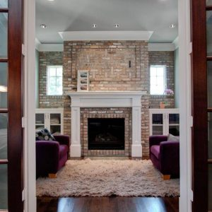 Area Shag Rug And Brick Fireplace Also Brick Wall With Fireplace Mantles Plus Built In Storage And Ceiling Lighting Also Crown Molding In Traditional Family Room With Purple Couch