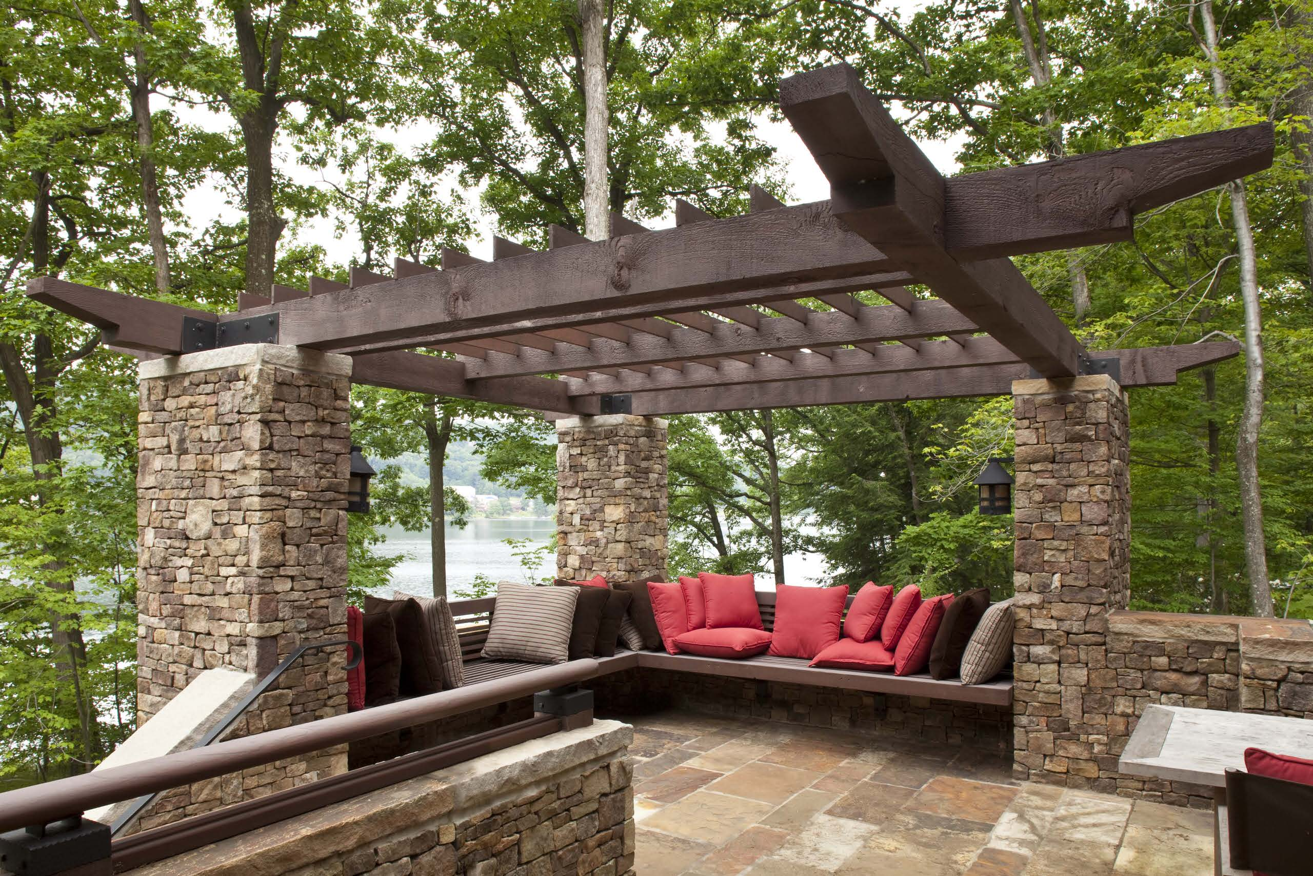 Inspiring Exterior House plus Pergola Ideas: Arts And Crafts With Built In Bench Plus Cantilever And Cross Beams With Dark Wood Pergola And Outdoor Cushions For Outdoor Living With Pergola Ideas And Stone Veneer Columns Plus Waterfront
