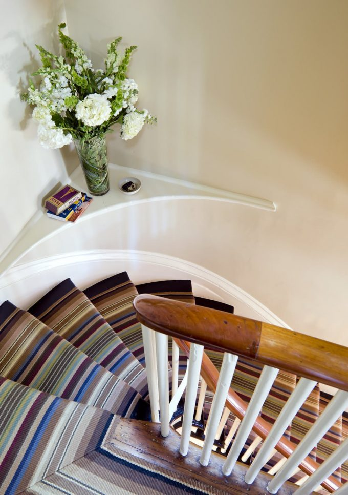 Banister With Curved Stair And Custom Rug Also Floral Arrangement On Corner Floating Shelf Plus Handrail With Playful And Stark Carpet Also Striped Rug With Wood Flooring For Staircase