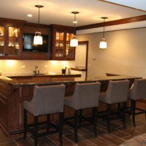 Bar Counter Height And Basement Seating Plus Basement Cabinet In Traditional Basement With Ceramic Tile That Looks Like Wood Plus Pendant Lighting And Under Cabinet Lighting