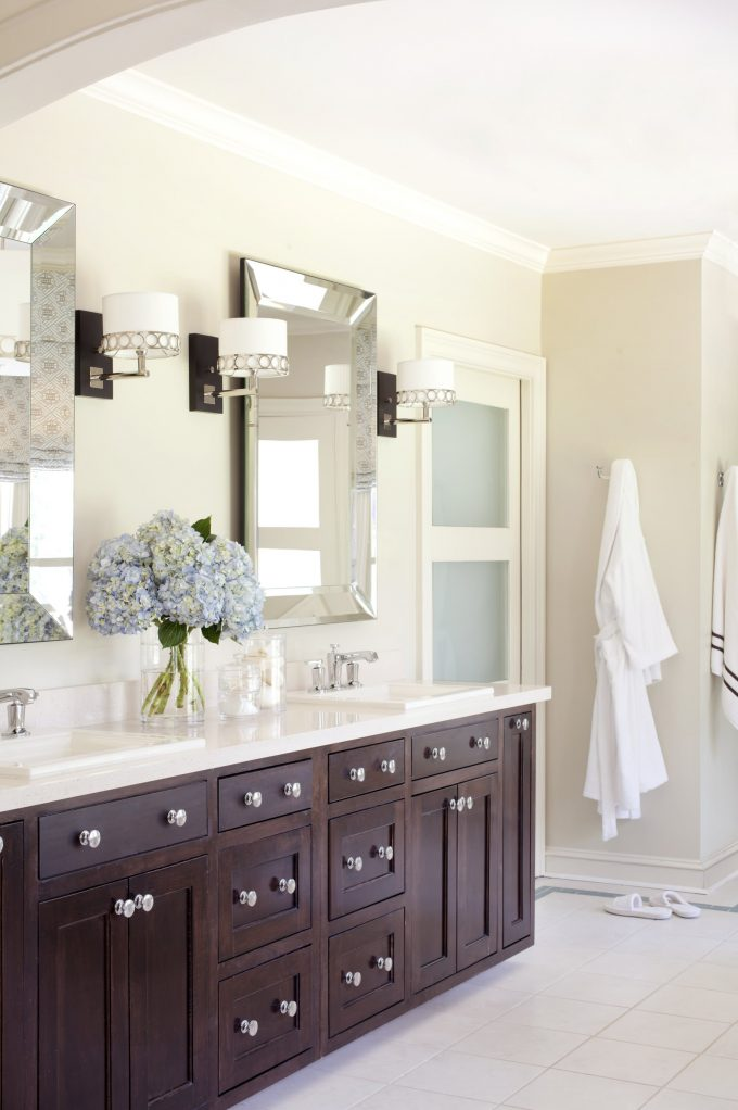 Baseboards In Transitional Bathroom Plus Bathroom Hardware And Bathroom Lighting With Beveled Mirror Also Dark Wood Cabinets Plus Floral Arrangement With Neutral Colors And Sconce Also Square Sink