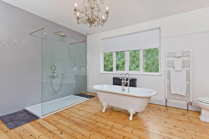 Bathroom Chandeliers And Window Treatments With Claw Foot Tub And Glass Shower Also Subway Tile Walls And Shower Pan With Bath Mats Plus Wood Flooring And Towel Rack