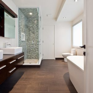 Bathroom Mirror In Rustic Bathroom With Ceramic Tile That Looks Like Wood And Ceiling Lighting Plus Floating Dark Wood Cabinets With Double Sinks And Freestanding Tub Plus Walk In Shower