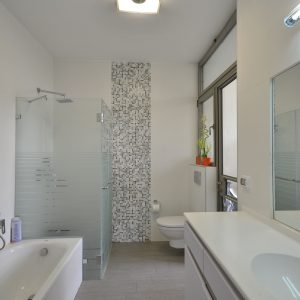 Bathtub And Frosted Glass Shower Plus Small Tile Accent Wall With Tall Ceiling In Contemporary Bathroom Plus Vanity Storage And Glass Shower Enclosures Plus Modern Sink On White Counter