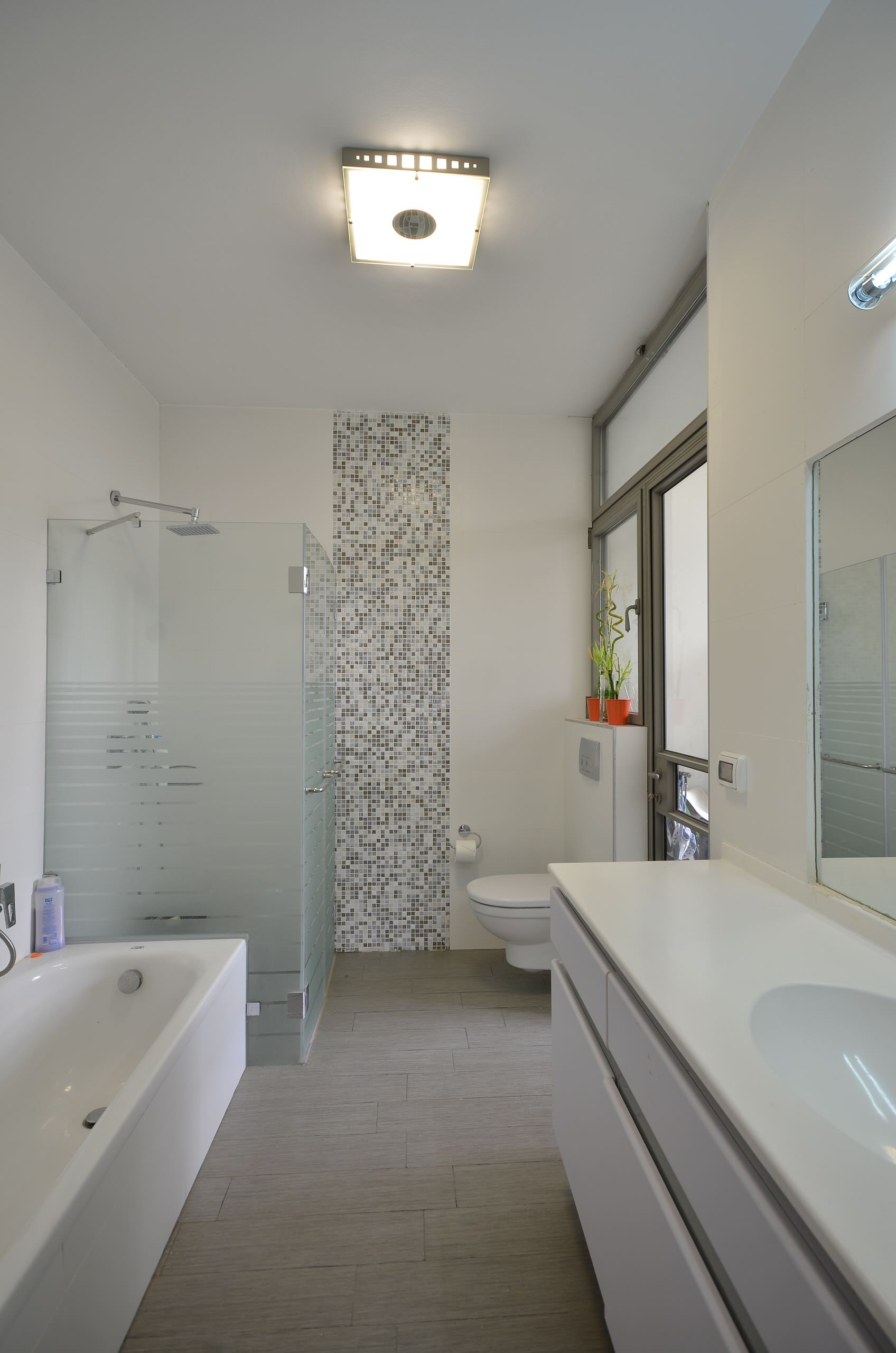 Remodel Bathroom Ideas Using Glass Shower Enclosures: Bathtub And Frosted Glass Shower Plus Small Tile Accent Wall With Tall Ceiling In Contemporary Bathroom Plus Vanity Storage And Glass Shower Enclosures Plus Modern Sink On White Counter