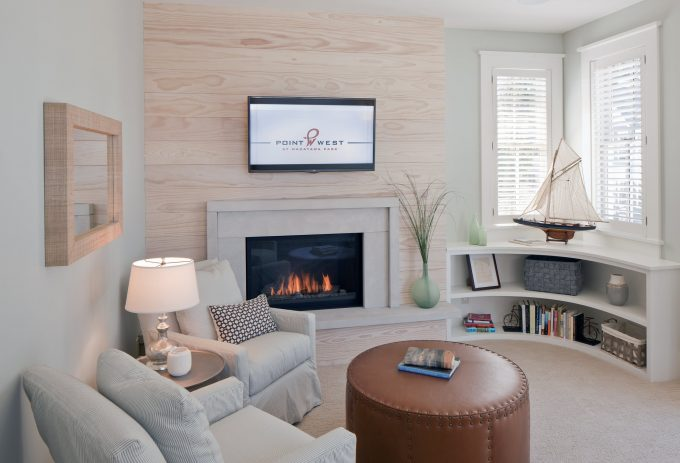 Bedroom Sitting Area With Slipcover Armchairs And Leather Drum Ottoman Also Curved Bookshelf With Gas Fireplace And Natural Wood Plus Television Above Fireplace Also Corner Shelf Unit