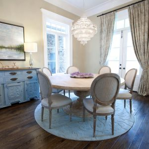 Beige Dining Chair And Light Wood Dining Table On Round Rug Plus Buffet Lamps On Blue Sideboard In Traditional Dining Room Plus Crystal Chandelier And Dark Wood Flooring With Double Door