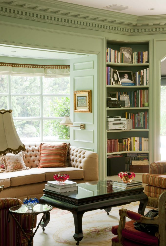 Beige Tufted Sofa In Traditional Living Room Plus Built In Bookshelves And Dark Coffee Table With Glass Top Also Light Green Molding And Light Green Wall Plus Corner Shelf Unit With Patterned Armchair