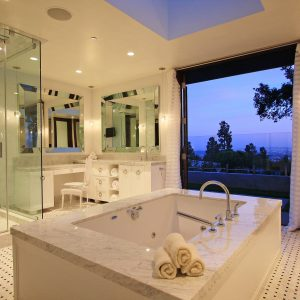 Beveled Mirror Plus Ceiling Lighting And Dressing Table In Contemporary Bathroom With Floor Tile Design And Glass Shower Enclosure Plus Rain Shower Head And Tub Surround