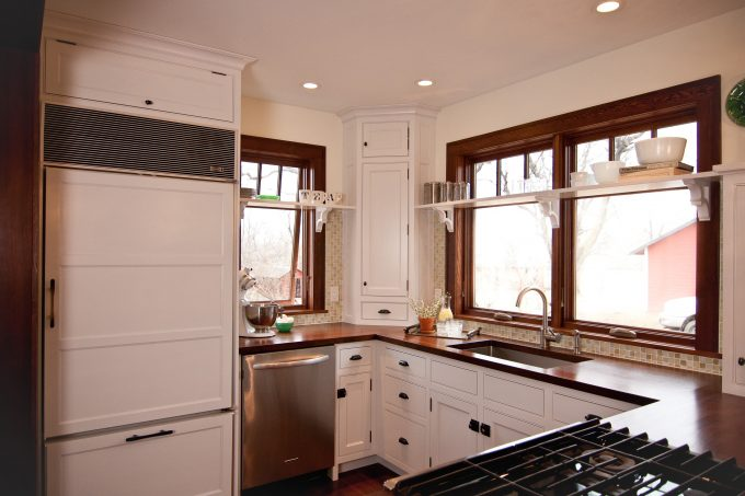 Bin Pulls On Cabinet Latch In Farmhouse Kitchen Plus Corner Shelf Unit With Crown Moulding Also Dark Wood Casing And Double Hung Windows With Recessed Lighting And Hardwood Flooring