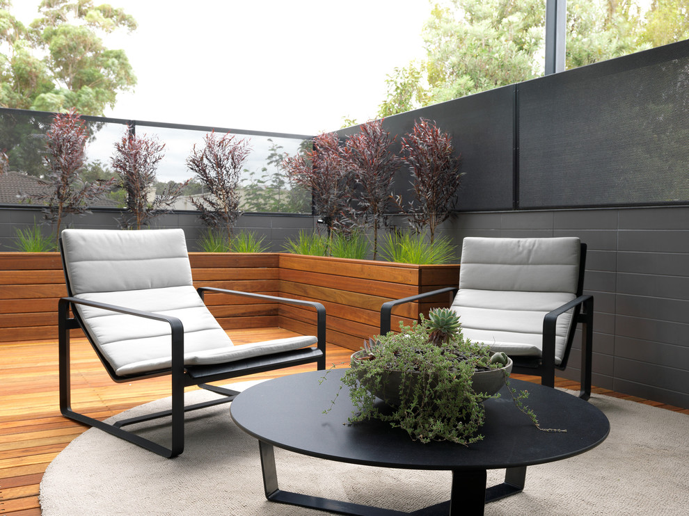 Black Coffee Table Plus Bowl Plant And Planter Boxes Also Grasses With Gray Wall And Horizontal Planks Plus Lounge Chairs In Roof Deck With Outdoor Round Rug For Contemporary Patio