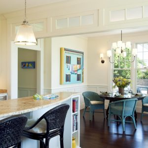 Blue Chairs And Bookshelves On Breakfast Bar Plus Breakfast Nook With Chair Cushions And Chandelier Also Dark Wood Flooring With Floral Arrangement On Round Dining Table Plus Transom Windows