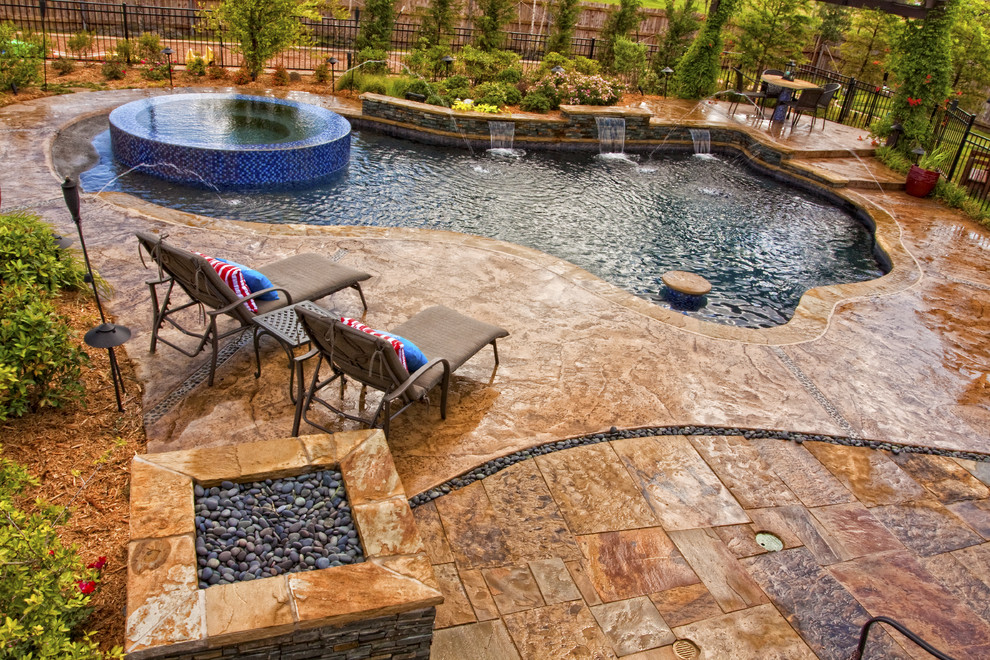 Top Materials for Patio Using Stamped Concrete Patio: Blue Glass Tile For Freeform Pool Also Lagoon Pool With Flagstone Plus Negative Edge Spa And River Rock Also Stamped Concrete Patio In Eclectic Pool Plus Outdoor Chaise Lounge Chairs