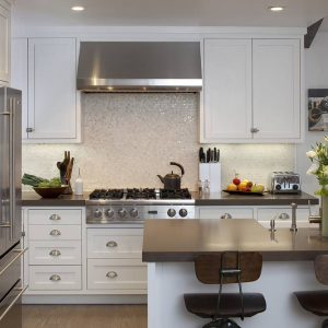 Breakfast Bar And Ceiling Lighting Plus Kitchen Hardware With Neutral Colors And Range Hood Also Backsplashes Plus Recessed Lighting And Stainless Steel Appliances In White Kitchen
