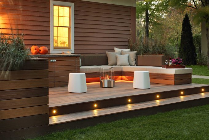 Brown Siding Plus White Trim Window Also Outdoor Living Space With Deck Outdoor Fireplace And Gray Pillows On Bench Plus Seat Cushion Also Ottoman Tray With Pumpkins Decor And Stair Lighting