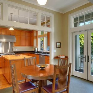 Butcher Block In Craftsman Kitchen With Crown Molding And Transom Windows Plus French Doors With Kitchen Island And Mission Furniture Plus Red Leather Seat Cushions Also Round Dining Table