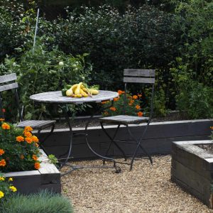 Cafe Chairs And Round Table For Outdoor Dining With Edible Garden Plus Gravel Path And Orange Flowers Also Flower Bed With Vegetable Garden And Container Plant In Traditional Landscape