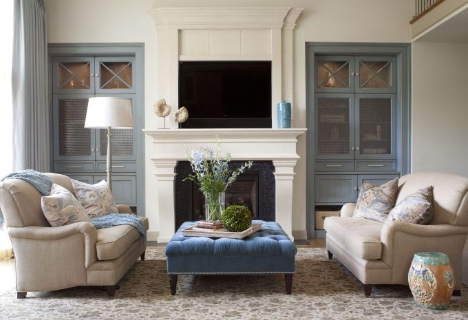 Carpeting And Blue Cabinets Plus Ceramic Stool Also Limestone Fireplace With Fireplace Mantels In Living Room Plus Transitional Design And Tufted Ottoman Also Tv Above Fireplace
