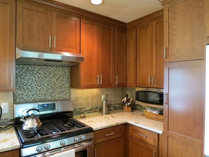 Cherry Cabinets And Dura Supreme With Glass Tile Backsplash Plus Stainless Hood Also Under Cabinet Microwave In Traditional Kitchen With Recessed Lighting Plus Under Cabinet Lighting