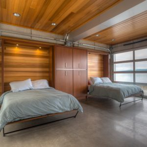 Contemporary Bedroom With Wooden Ceiling And Recessed Lighting Also Murphy Bed With Bedding And Built In Armoire Plus Polished Concrete Flooring
