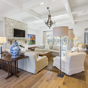 Contemporary Family Room With Area Rug And Engineered Wood Flooring Plus Artwork And Coffered Ceiling Also Chandelier With Floor Lamp And Seating Area Also Slipcovers Plus Stone Fireplace With Wall Mount Tv