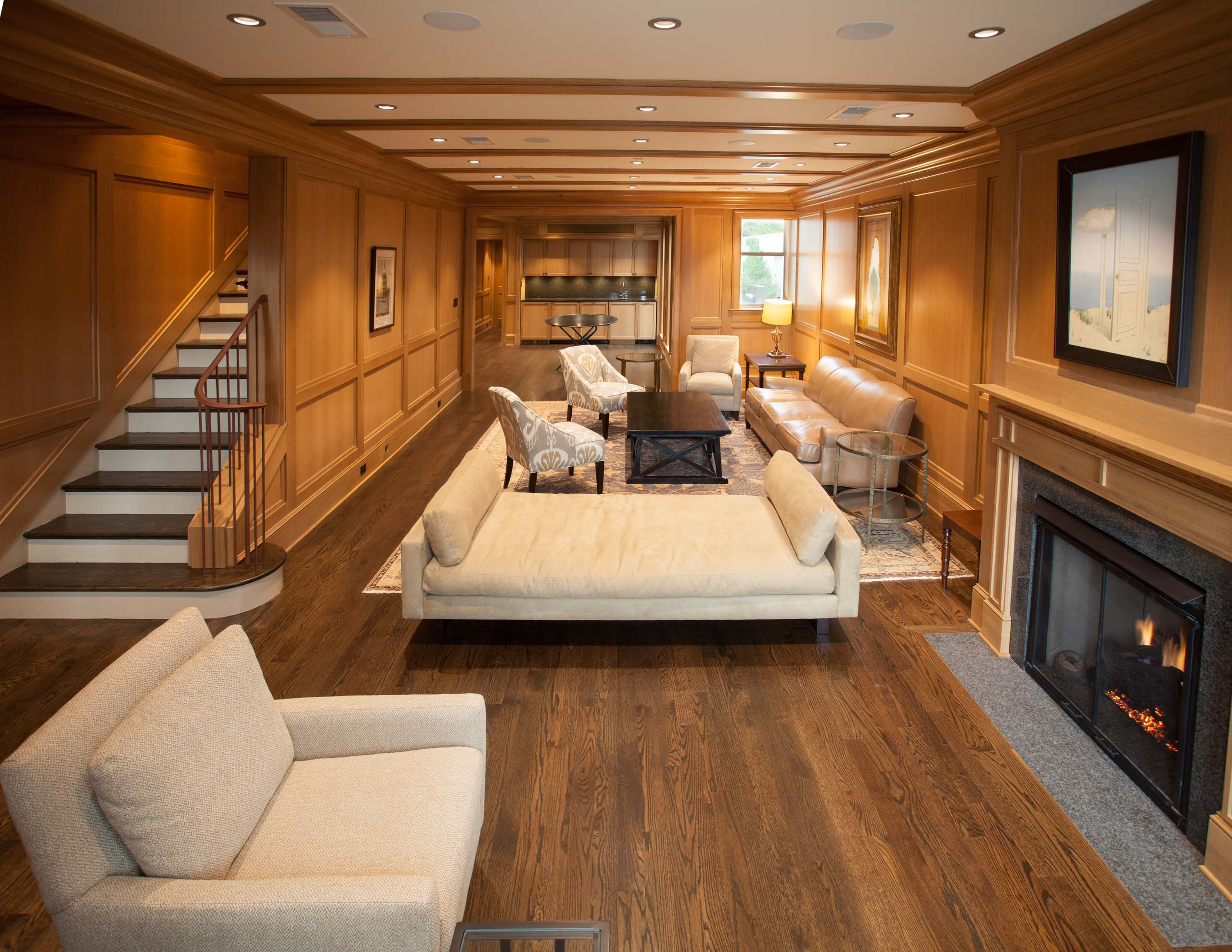 Contemporary Living Room With Multiple Seating Areas And Modern Daybed On Red Oak Flooring Plus Granite Fireplace And Large Television Also Iron Handrail Add Recessed Lighting