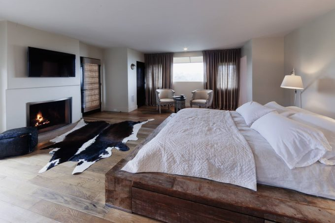 Cowhide Rug In Master Bedroom With Neutral Colors And Reclaimed Wood Bed For Platform Bed Plus Tv Above Fireplace Also Window Sheers With Wood Flooring For Rustic Bedroom