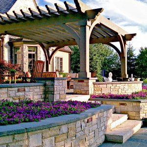 Cross Beams Also Curved Knee Braces With Pergola Plus Planters And Seat Walls For Terrace With Stone Walls Plus Flower Bed And Stone Flooring Also Stair With Outdoor Furniture In Modern Home