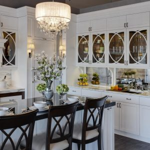 Crystal Chandelier Also Counter Stools Plus Glass Front Cabinets With Gray Vaulted Ceiling And Marble Counters Plus Padded Chairs On Tile Floor With Track Lighting And Refacing Kitchen Cabinets