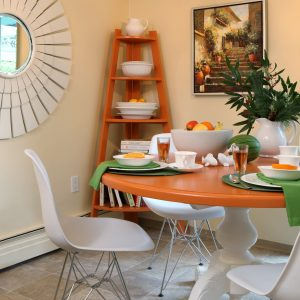 Crystal Chandelier And Eiffel Chairs In Kitchen Dining Area Plus Corner Shelf Unit Also Sunburst Mirror And Wall Decor With Tangerine Round Table Also Taupe And Peach Lino Flooring Plus Yellow Walls