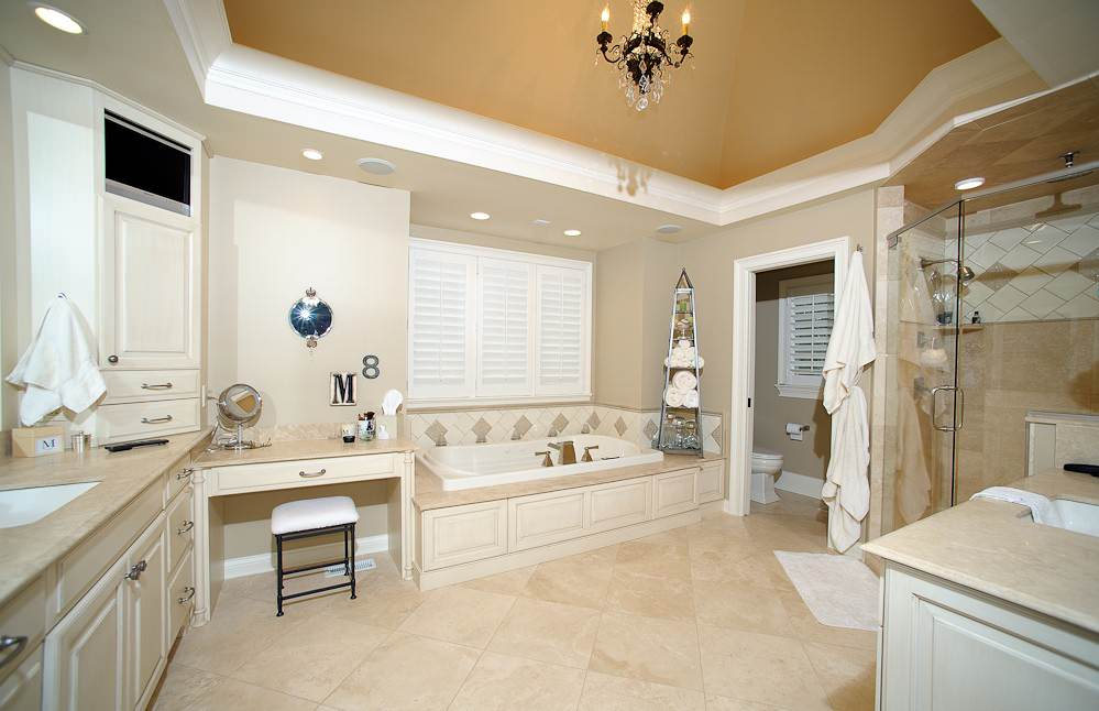 Interior Design Ideas with Crema Marfil Marble from Turkey: Crystal Chandelier In Traditional Bathroom With Crema Marfil Marble Plus Soaking Tub Also Vanity Stool And Bathroom Storage Ideas With White Painted Trim And Walk In Shower Ideas