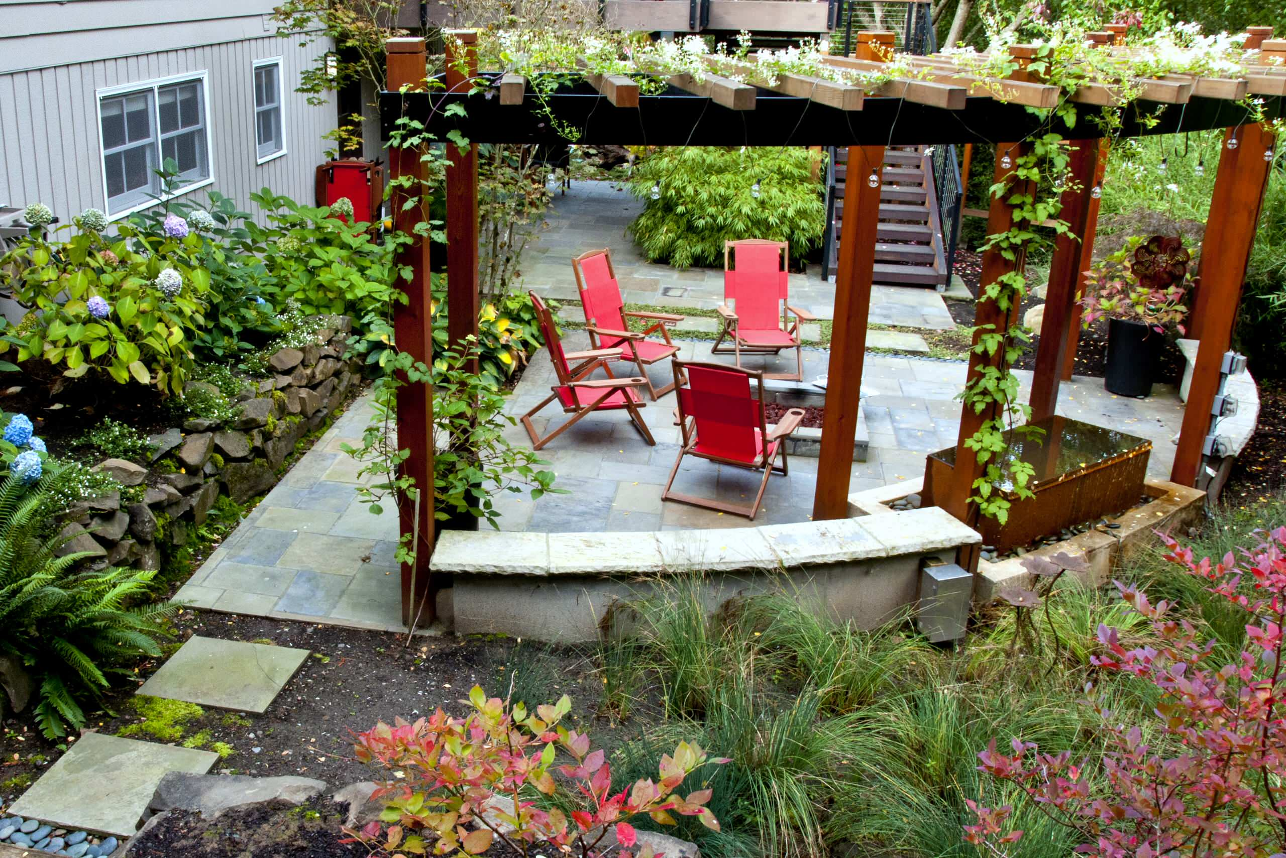 Inspiring Exterior House plus Pergola Ideas: Curved Garden Wall Plus Fire Pit And Flagstone Also Folding Chairs With Hydrangea For Pergola Ideas Also Rain Garden Plus Tall Grasses With Water Feature And Climbing Plants On Arbour