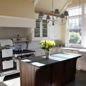 Dal Tile In Industrial Kitchen Plus Layout Chandelier And Flower Arrangement On Wood Kitchen Island With Stone Tile Flooring And Custom Exhaust Hood Also Glass Front Cabinets