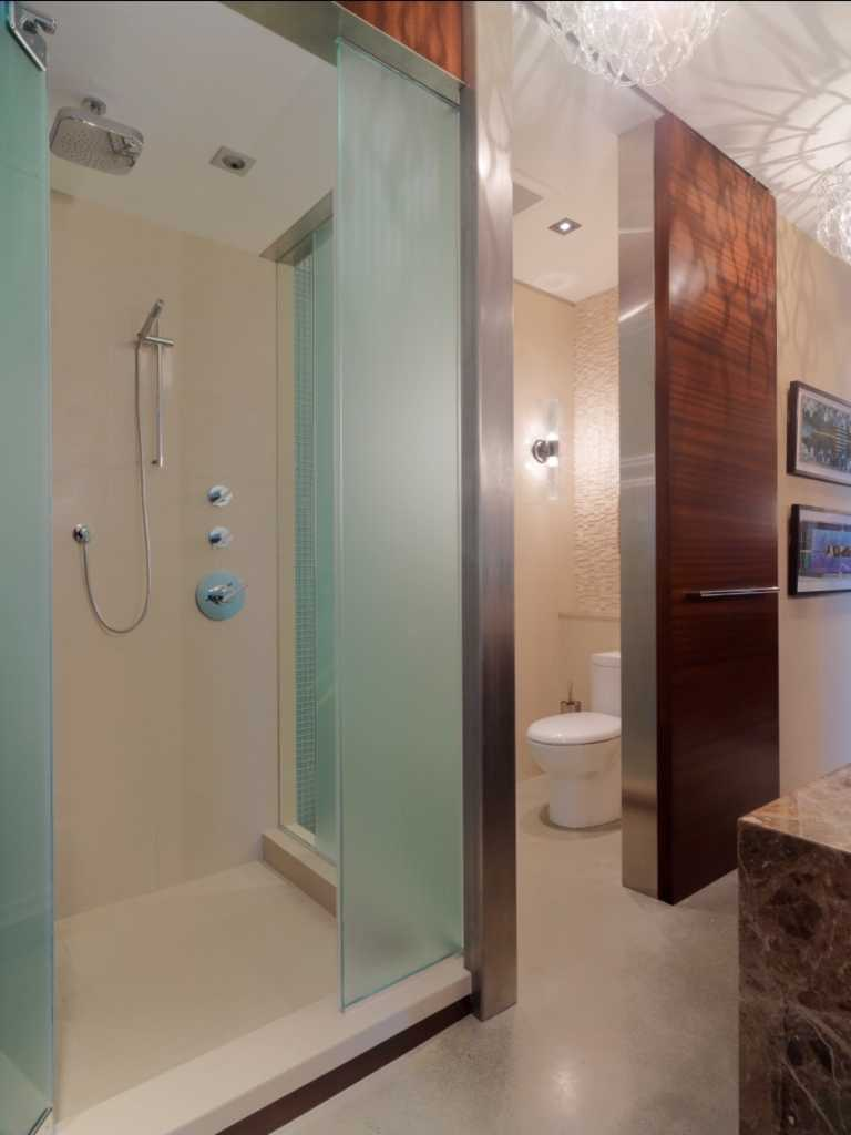 Inspiration for Remodeling Bathroom Using Water Closet: Frosted Glass And Walk In Shower With Open Shower And Rain Shower Head In Rustic Bathroom Plus Sconce And Wall Decor Also Water Closet With Contemporary Chandelier And Wood Paneling