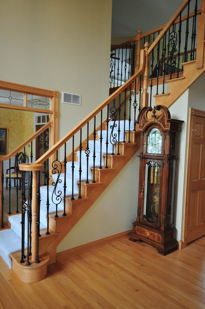 Grandfather Clock And Traditional Staircase Plus Iron Railings Also Wrought Iron Ballisters With Light Wood Flooring And Tall Ceiling Also Spindels Plus Modern Doors In Modern House