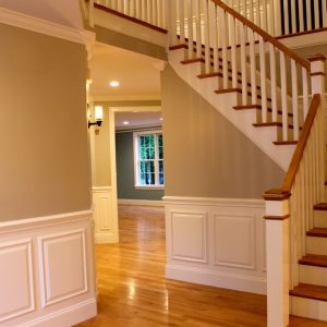 Hallway Staircase With Wood Handrail And Wainscoting Plus Red Oak Flooring Add Raised Panel Trim And Rubbed Bronze Hardware Completed By Sconce Hall Lighting