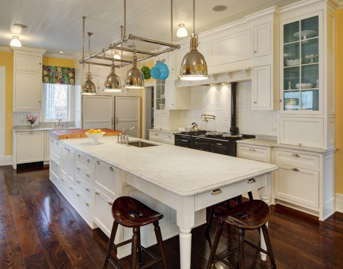 Hanging Metal Lights With Marble Counters Plus Wood Bar Stool On Oak Floors And Tongue And Groove Ceiling In Traditional Kitchen Plus White Shaker Cabinets And Under Cabinet Lighting
