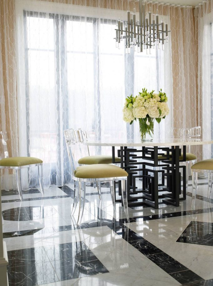 Interesting Black And White Marble Flooring In Breakfast Room Plus Contemporary Chandelier And Flower Arrangement With Lucite Chairs On Pattern Floor Also Sheer Drapes On Window Treatment